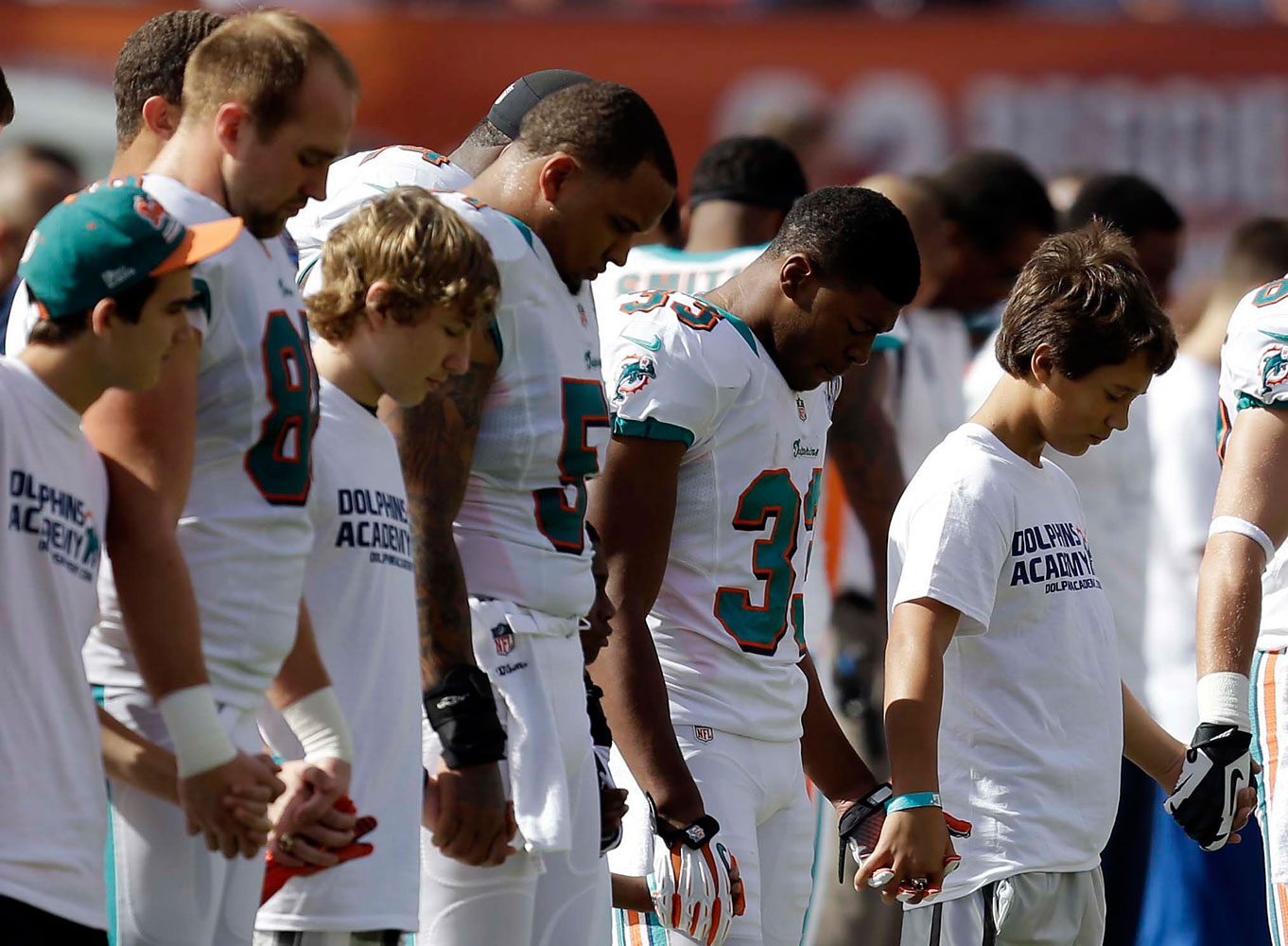 image: Miami Dolphins and young football players hold hands during a moment of silence for the victims of Friday's Sandy Hook Elementary School shootings