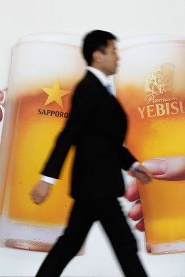 Image: A man walks past a poster of Sapporo Holdings' beer at the company's lobby in Tokyo February 16, 2011.
