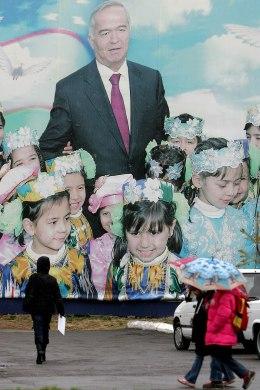 Image: People walk in front of a giant poster of Uzbek President Islam Karimov in Tashkent, 24 December 2007.