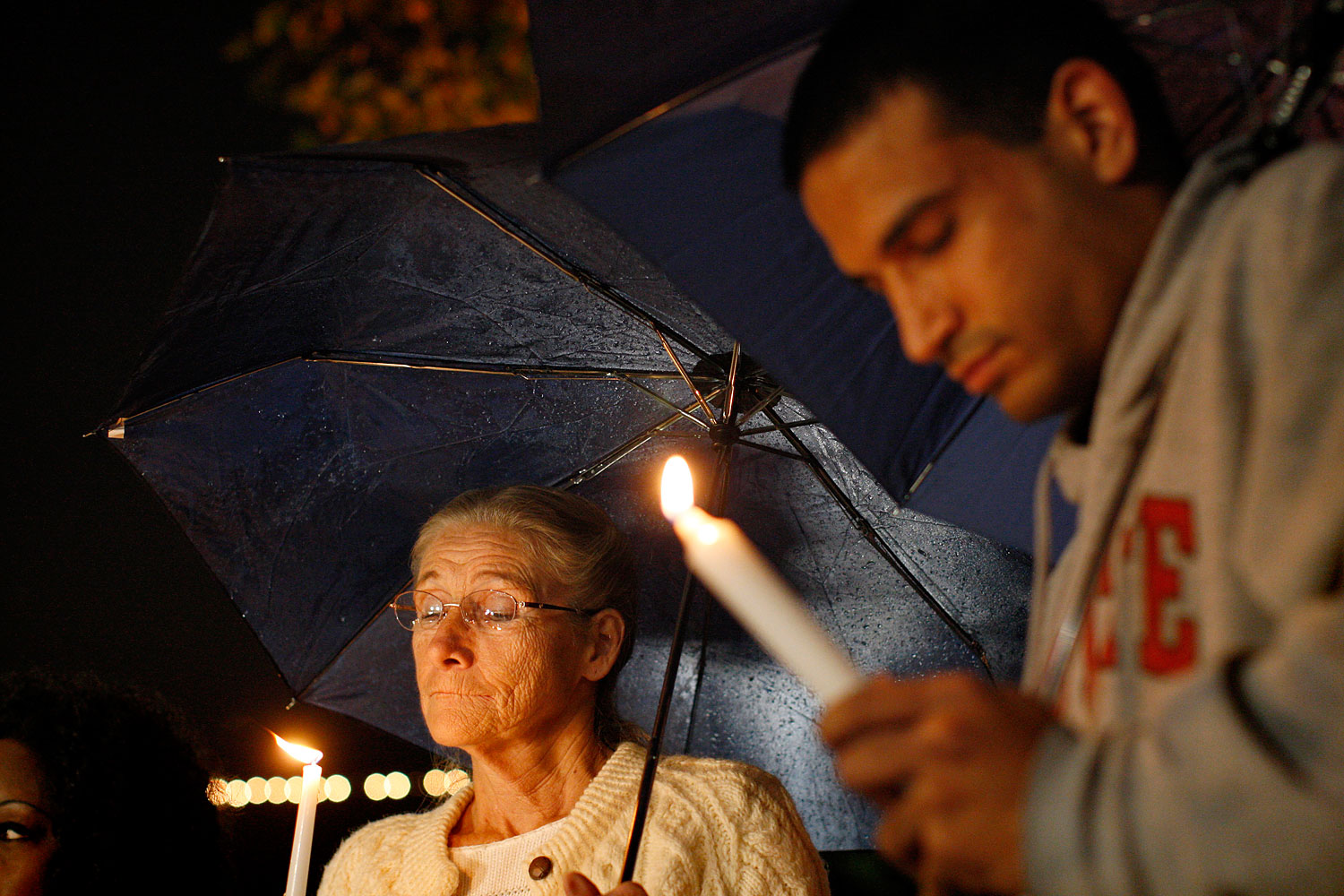 image: Doreen Finsinger and Raagir Quraishi pray during a candlelight vigil in memory of those killed in a mass shooting at Sandy Hook Elementary School in Connecticut, in Los Angeles, California