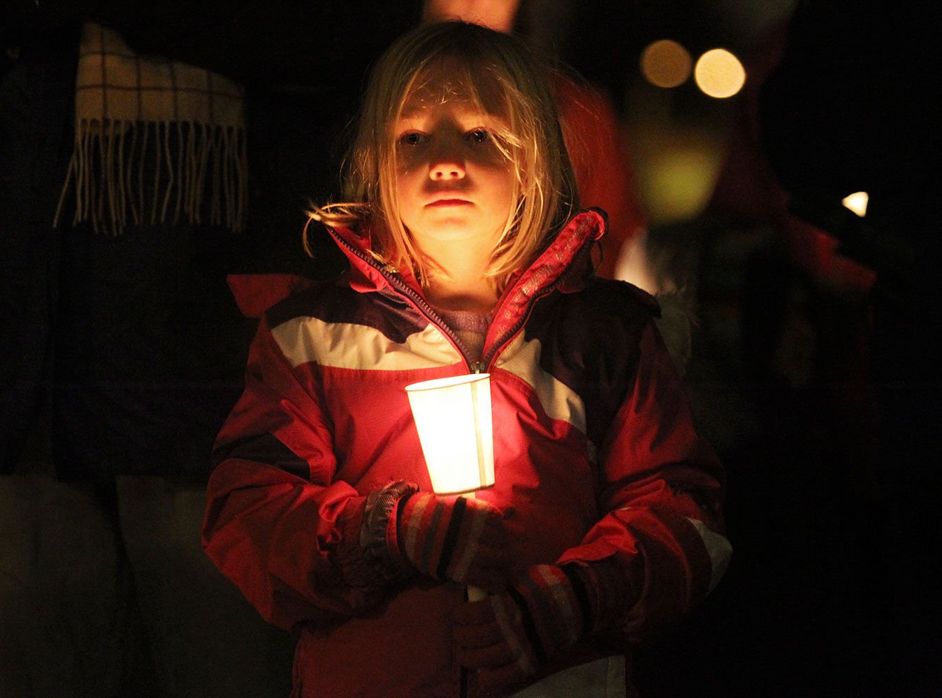 image: Noble holds a candle while attending a vigil for victims of a Connecticut school shooting, in Seattle