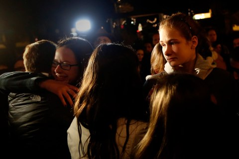 image: People grieve outside the overflow area of a vigil at the Saint Rose of Lima church for victims of a shooting at Sandy Hook Elementary School in Newtown, Conn., Dec. 14, 2012.