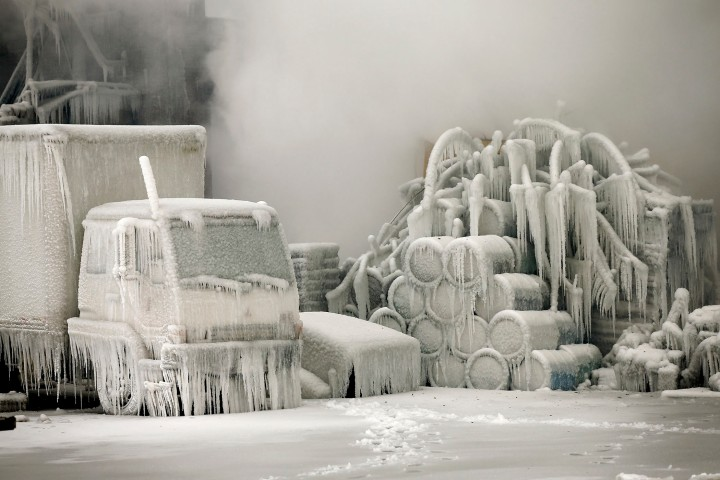 A truck is covered in ice as firefighters help to extinguish a massive blaze at a vacant warehouse on Jan 22, 2013 in Chicago. More than 200 firefighters battled a five-alarm fire as temperatures were in the single digits.