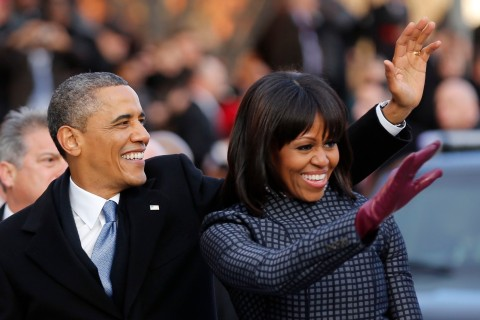 image: President Barack Obama and first lady Michelle Obama walk and wave after emerging from the presidential limousine during the inaugural parade from the Capitol to the White House in Washington, Jan. 21, 2013.