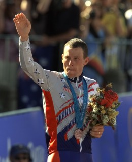 image: Lance Armstrong waves after receiving the bronze medal in the men's individual time trials at the 2000 Summer Olympics cycling road course in Sydney, Australia, Sept. 30, 2000.