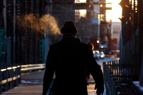 A man's breath condenses as he walks in single digit temperatures on a cold morning in Boston