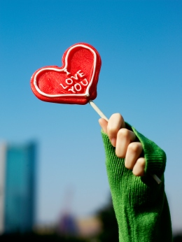 Image: A woman's hand holding up a red heart-shaped lollipop.