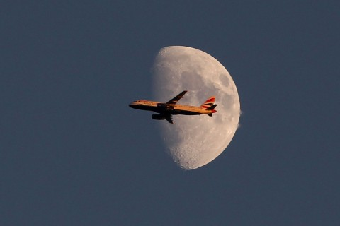 LONDON, ENGLAND - JUNE 28: A view of a British Airways plane flying past the moon over day four of the Wimbledon Lawn Tennis Championships