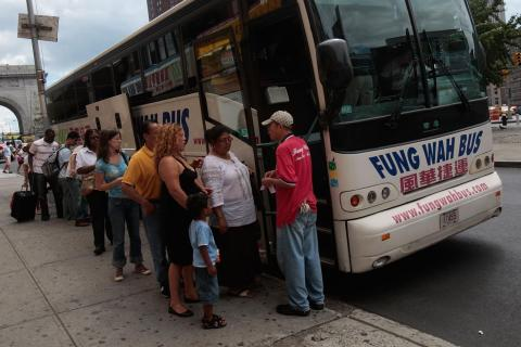img: Passengers line up to board a Fung Wah bus headed for Boston on August 4, 2008 in New York City.
