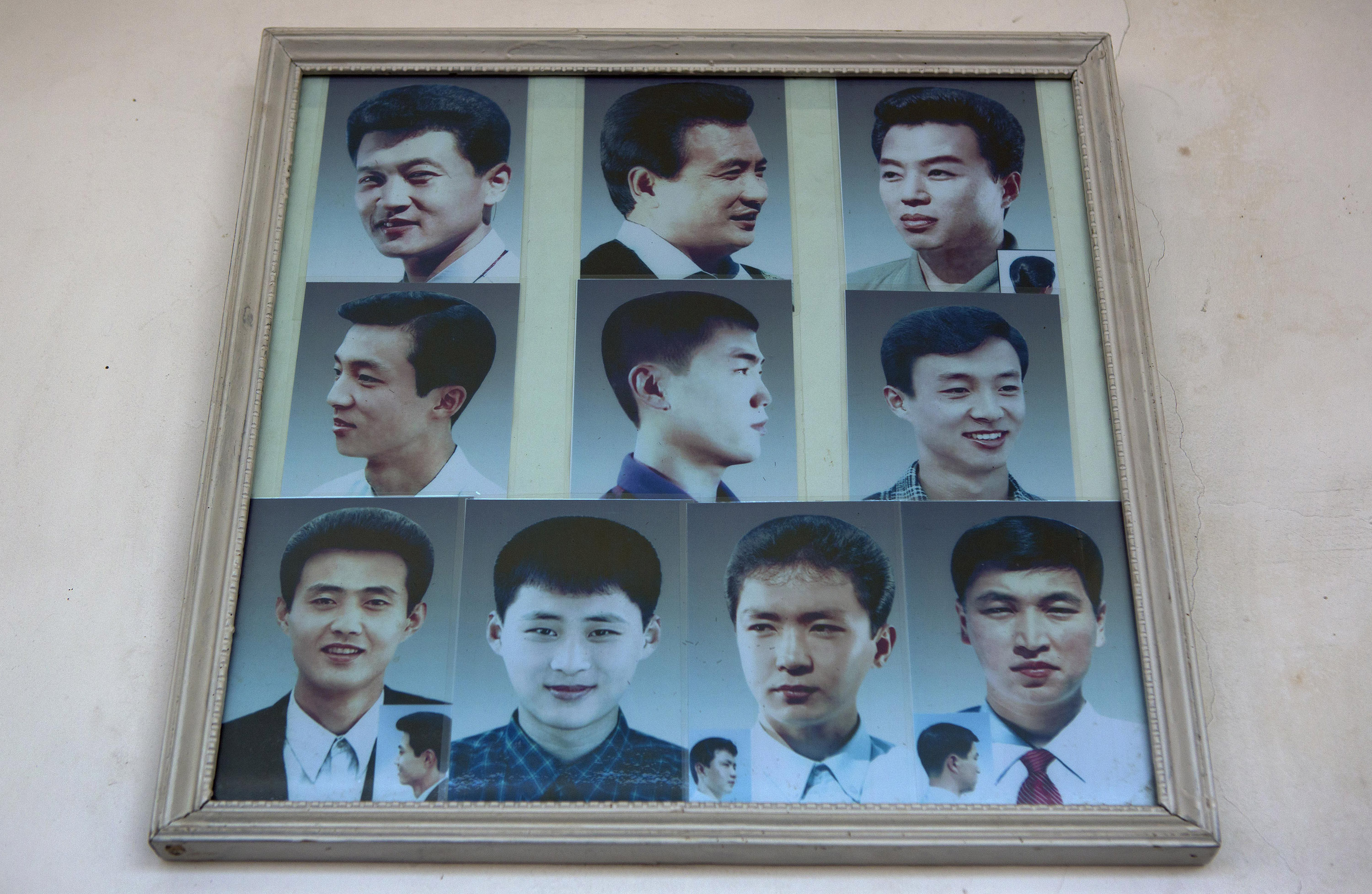 Photos showing example hair styles hang inside a barber shop in Pyongyang, North Korea on Feb. 20, 2013.