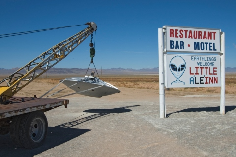 Flying saucer hooked up to tow truck and motel sign, Extraterrestrial Highway.