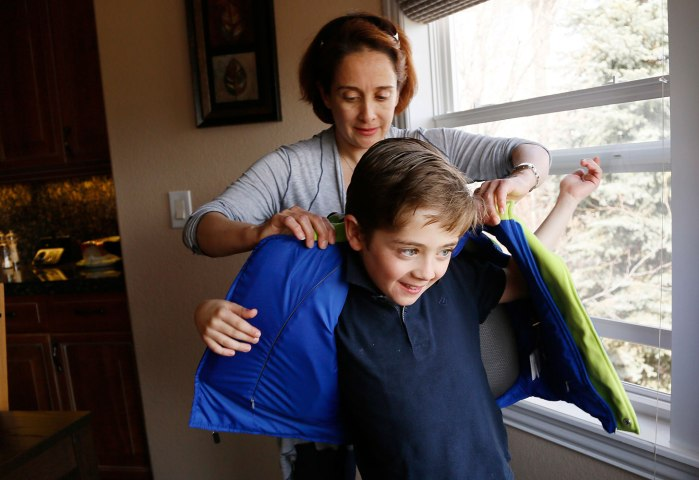 Sheirn Adi helps her son Bilal put on a bullet proof vest backpack combination called the V-Bag sold by Elite Sterling Security LLC in Aurora