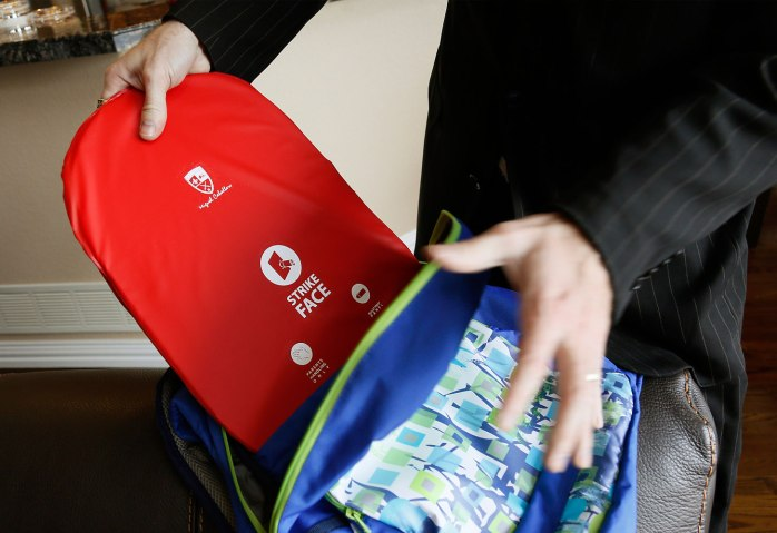 Timothy Hogan, COO of Elite Sterling Security, LLC  shows the bullet proof plate inside the company's children's backpack product in Aurora