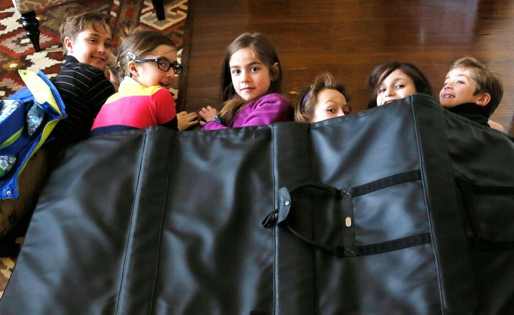 Children demonstrate how they might take shelter in a school under a bullet proof blanket sold by Elite Sterling Security LLC in Aurora