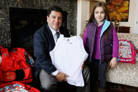 Miguel Caballero, CEO of the Miguel Caballero Company holds an armored tank top as he poses with Lana wearing a MC Kids Ballistic Puffer Vest both sold by Elite Sterling Security LLC in Aurora