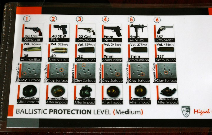 """Timothy Hogan, COO of Elite Sterling Security, LLC shows a chart of the various calibers of bullets the company's """"medium"""" level protection bullet proof products will stop in Aurora"""