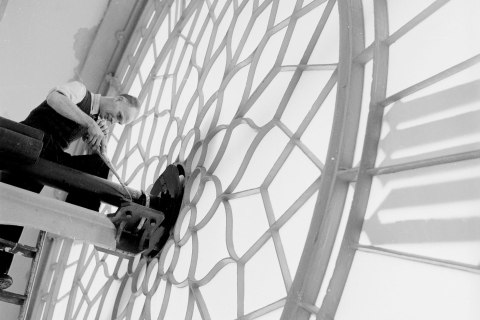 Technician Charles King carries out maintenance work behind the great clock face of Big Ben in the Palace of Westminster, London, 1957.