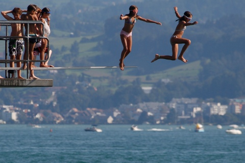 Teenagers jump into Lake Zurich on a hot sunny summer day in Kuesnacht