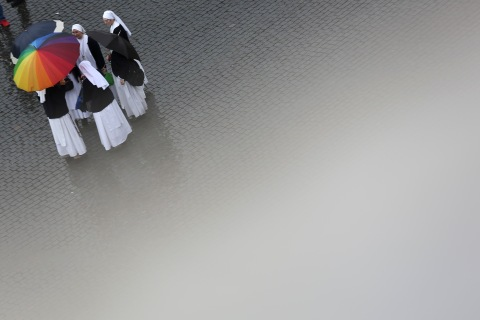 Nuns hold umbrellas in Saint Peter's Square while waiting for the smoke from the chimney of the Sistine Chapel in the Vatican City