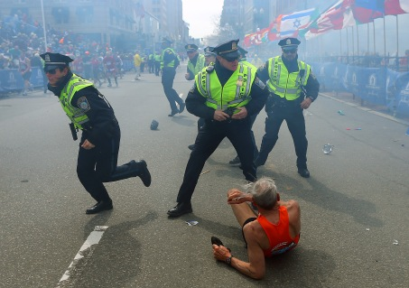 Police officers draw their weapons after hearing a second explosion near the finish line of the 117th Boston Marathon on April 15, 2013.