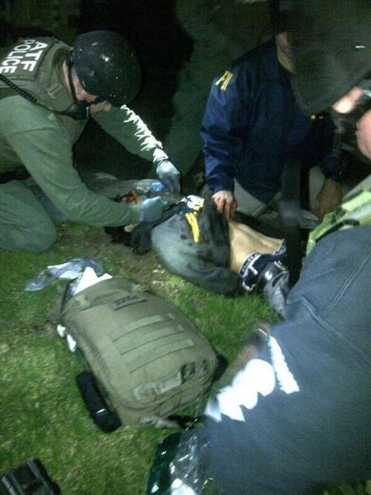 Handout photo of Dzhokhar Tsarnaev being searched by law enforcement officers