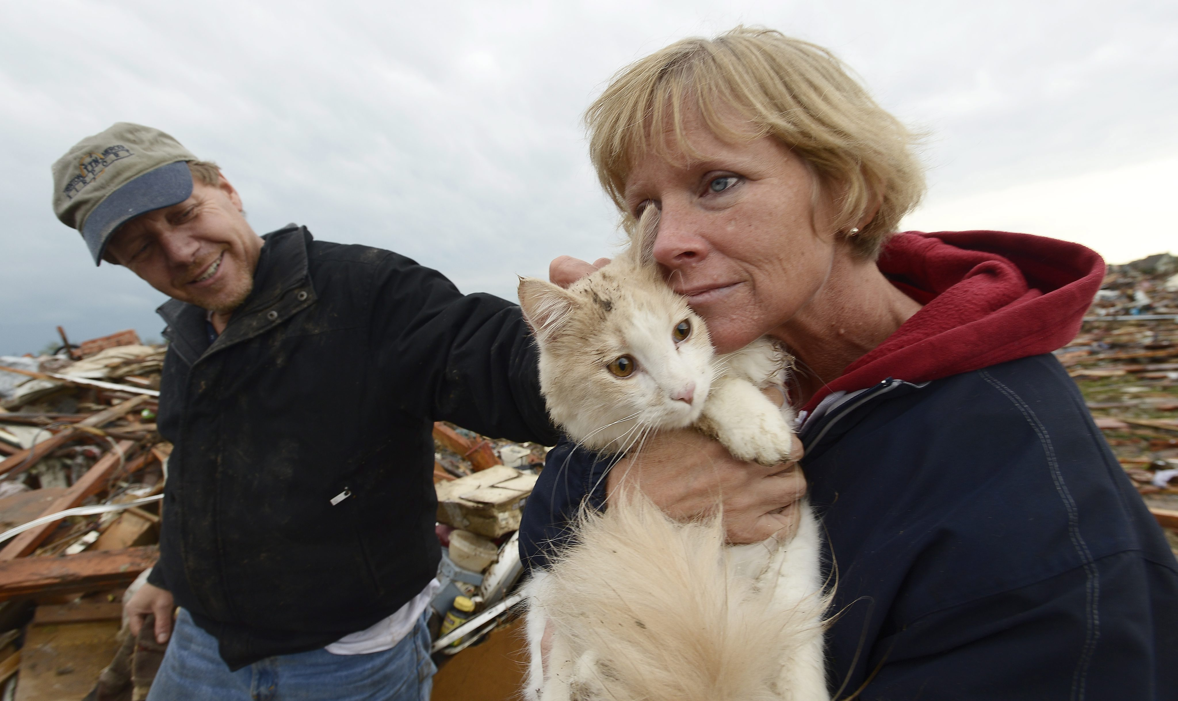 From left: Eric and June Simson hold their cat 'Sammi' seconds after finding it in the rubble of their home in a destroyed neighborhood in Moore, Okla., May 21, 2013.