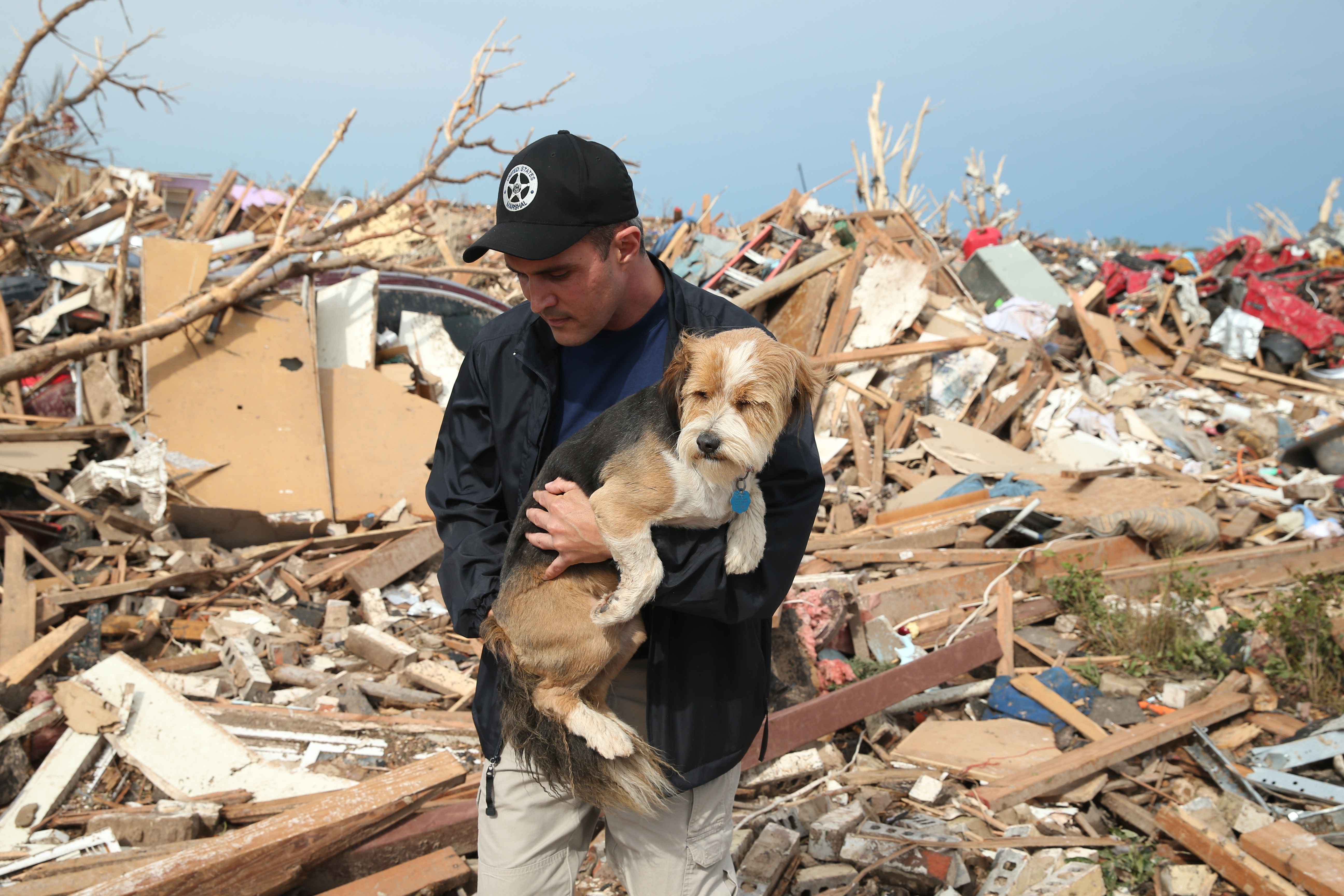 Sean Xuereb recovers a dog from the rubble of a home that was destroyed by a tornado on May 21, 2013 in Moore, Okla.