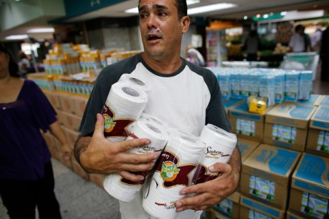 A man stocks up on toilet paper at a supermarket in Caracas, on May 17, 2013.