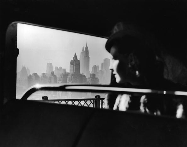 A female passenger looks out at the Empire State Building and the New York City skyline while traveling over the 59th Street Bridge, circa 1940s.