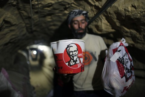 A smuggler carries food from Kentucky Fried Chicken to be delivered through an underground tunnel linking the Gaza Strip to Egypt, in Rafah, on May 13, 2013.