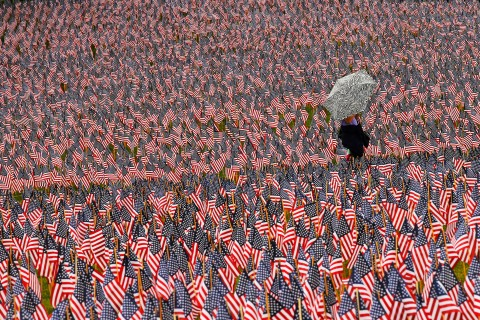 Pedestrian carrying an umbrella walks through a Memorial Day display of United States flags on the Boston Common in Boston