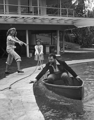 Actress Rita Hayworth clowning with husband Orson Welles, who is in a boat in their swimming pool, at home.