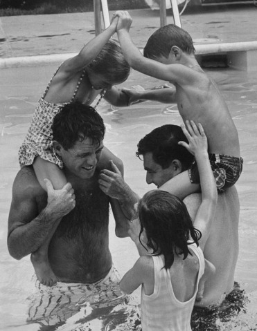From left: Robert Kennedy and Pierre Salinger playing with their children in the swimming pool.