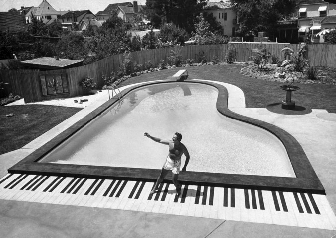Liberace at the 'piano' shaped pool in his home.