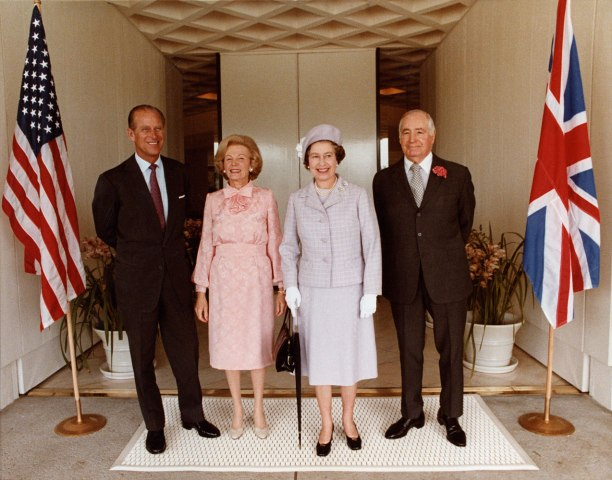 From left: Prince Phillip, Lee Annenberg, Queen Elizabeth II, and Walter Annenberg standing in front of the entrance to the estate house during the Queen's visit, February 1983.