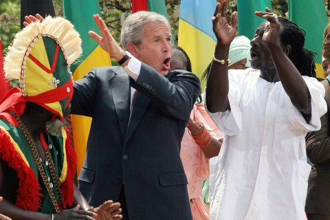 Former U.S. President George W. Bush dances with members of the Kankouran West African Dance Company in the Rose Garden of the White House in Washington, D.C., on April 25, 2007.
