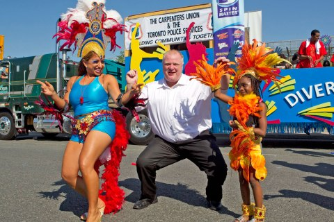 Toronto Mayor Rob Ford dances with participants at the Toronto Caribbean Carnival in Toronto, on July 30, 2011.