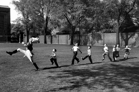 The drum major for the University of Michigan marching band rehearses as admiring children fall in line, 1950.