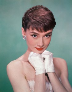 Portrait of Belgian-born American actress Audrey Hepburn as she wears a strapless gown and holds white kid-gloved hands up to her chin, early 1950s.