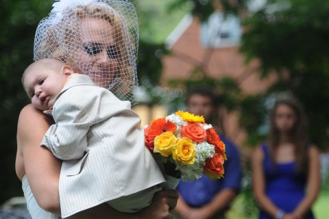 Christine Swidorsky carries her son and the couple's best man, Logan Stevenson, 2, down the aisle to her husband-to-be Sean Stevenson during the wedding ceremony in Jeannette, Pa., Aug. 3, 2013.