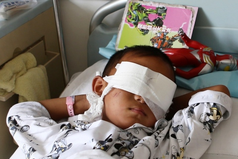 A boy whose eyes were gouged out lies on a hospital bed in Taiyuan