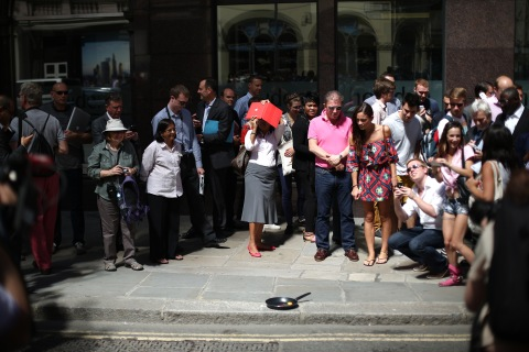 Crowds gather as a television crew tries to fry an egg in the glare from a new office building in the financial district on Sept. 4, 2013 in London.