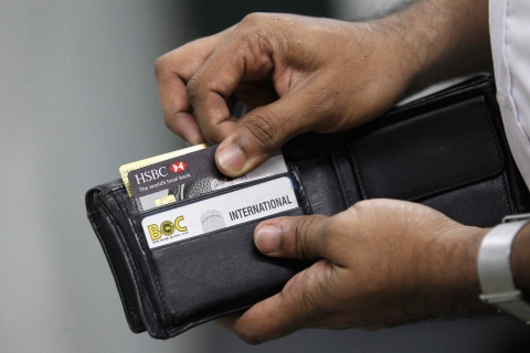 A man pulls out his credit card to make a purchase at a shop in Colombo