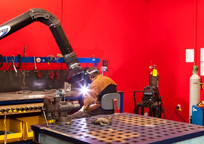 A man welds in the Google Workshops where Googlers recreationally explore hobbies such as machine making and woodworking.