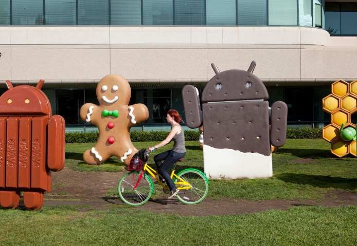 An employee rides a Google bicycle past Android-themed statues.