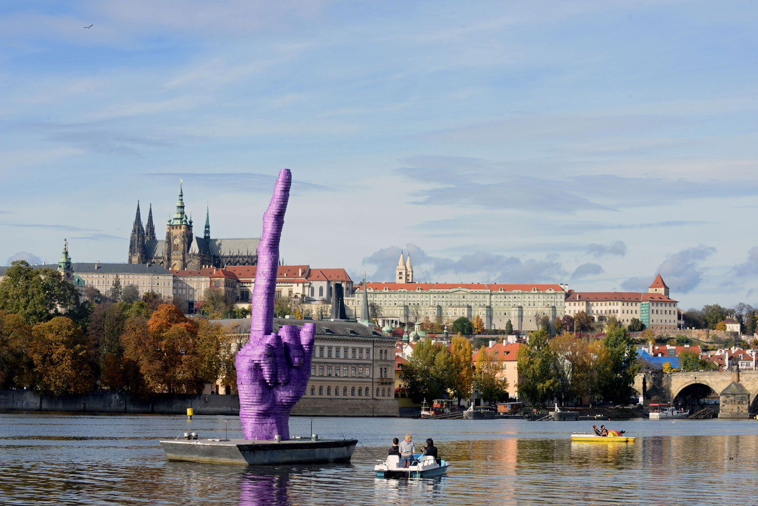 People sailing on the boats on Vltava River look at the giant purple middle finger sculpture by Czech artist David Cerny on October 21, 2013 in Prague.