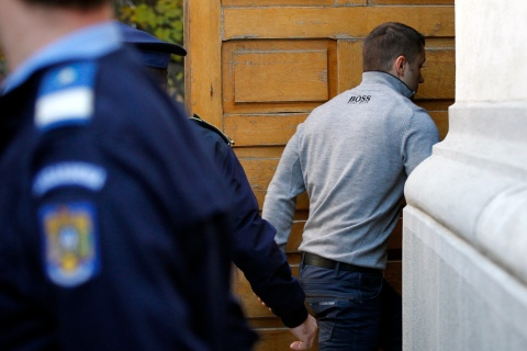 Dogaru, suspected ringleader in theft of seven paintings from Dutch museum, hides his face while arriving handcuffed and escorted by police for his trial at a court building in Bucharest