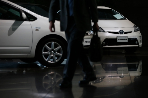 Toyota Motor Corp's successive models of Prius hybrid cars are displayed as a visitor walks past at the company's showroom in Tokyo