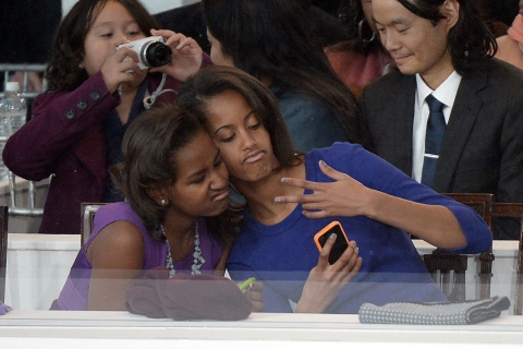 Sasha and Malia Obama, daughters of President Barack Obama, take selife during the Presidential Inaugural Parade on January 21, 2013 in Washington.