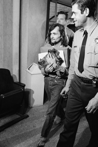Charles Manson, accused of seven killings including that of actress Sharon Tate, carries legal papers and an item of apparel as he leaves a Los Angeles courtroom, on Feb. 16, 1970 where he was denied a change of venue.